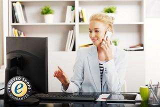 Junge Frau am Telefon vor Computer