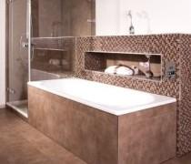 rotbraune Mosaikfliesen im Badezimmer an der Wand hinter einer Badewanne